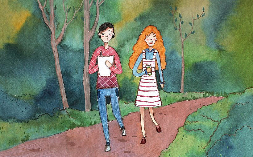A man and a woman walking along a trail laughing.