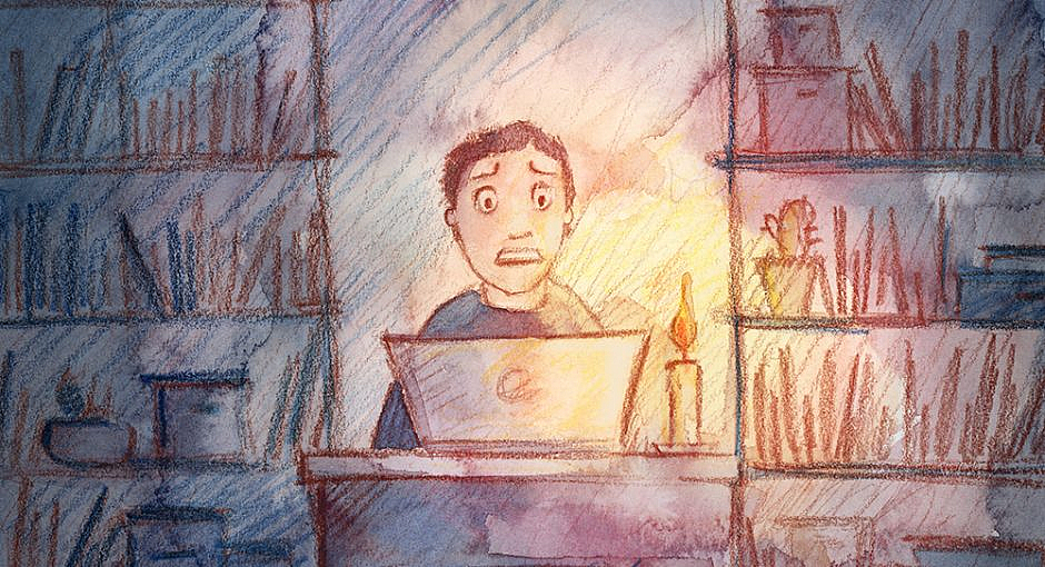 A man is sitting in front of a laptop in an office illuminated only by a candle with a scared look on his face.