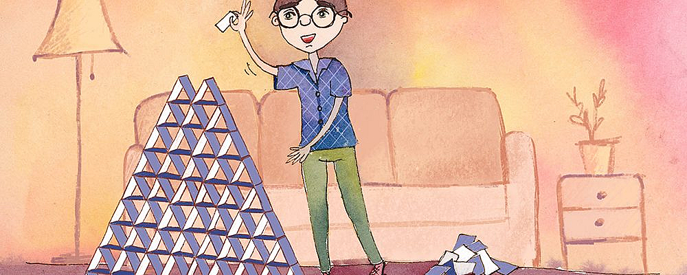 A man with glasses placing a card on top of a very large house of cards.