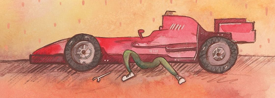 A sportscar with the legs of a person sticking out from under and a wrench by their side.